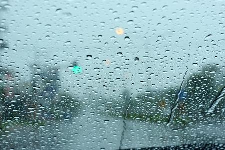 heavy rain: Road view through car window with rain drops  Stock Photo
