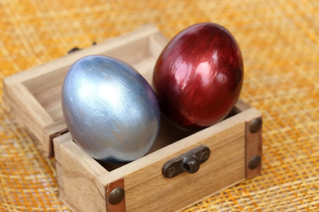 coffer: Colorful easter eggs in small coffer on bamboo weave sheet background. Stock Photo