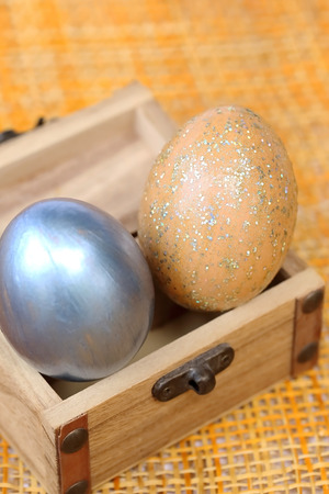 case sheet: Colorful easter eggs in wood case on bamboo weave sheet background.