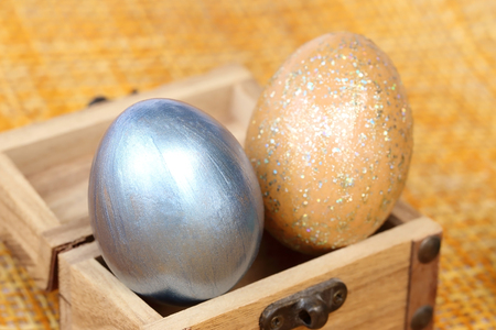 coffer: Easter eggs in small wood coffer on bamboo weave sheet background.