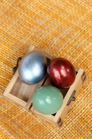 case sheet: Colorful easter eggs in small wood case on bamboo weave sheet background. Stock Photo