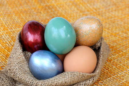 hessian: Colorful easter eggs in burlap hessian sacking bag.