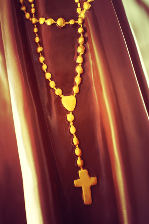 sacrosanct: Rosary beads or crucifix on statue, vintage style process.