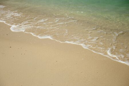 beach scene: Wave of the sea on sandy beach. Stock Photo