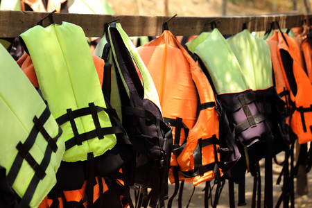 emergency vest: Colorful life jackets hanging on the row