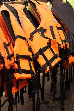 emergency vest: Life jackets hanging on the row Stock Photo