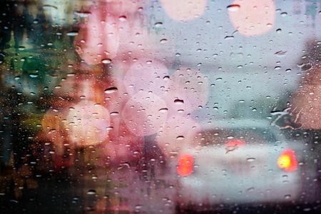 Driving in rain, raindrops on car window with light bokeh, rainy season abstract background. Stock Photo