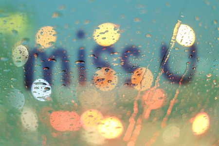 highway love: Rain drops and miss you text on window with light bokeh, rainy season abstract background.