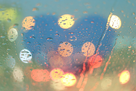 highway love: Rain drops and blurred heart write on window with light bokeh, rainy season abstract background.