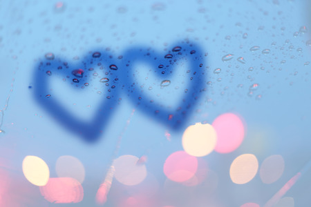highway love: Rain drops and two hearts write on window with light bokeh, rainy season abstract background. Stock Photo