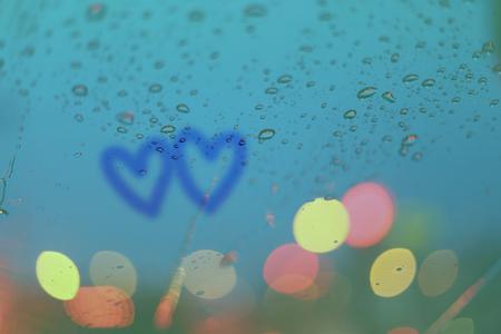 gotas de agua: Gotas de lluvia y dos corazones escribir en la ventana con el bokeh la luz, temporada de lluvias fondo abstracto. Foto de archivo