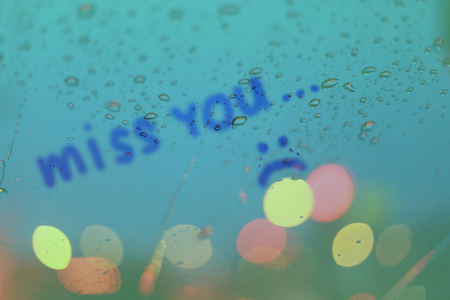 miss you: Rain drops with the word miss you write on window with light bokeh, rainy season abstract background.