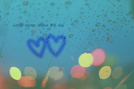 rain window: Inspirational Typographic Quote - Little things makes big day. Rain drops and two hearts write on window with light bokeh, rainy season abstract background.