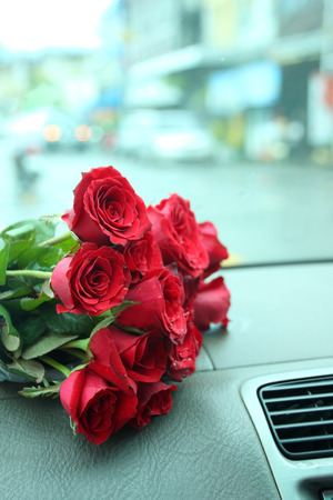 greetings card: Red roses bouquet on car console. Stock Photo