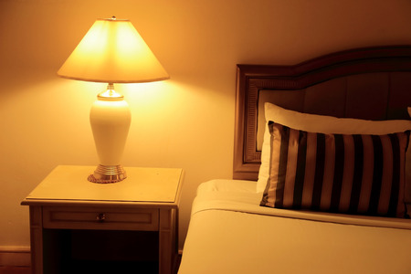 bedside lamp: Night scene image of hotel room interior, comfortable bed, pillows and lamp.