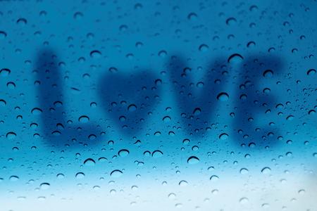corazones azules: La palabra amor sobre el vidrio con gotas de lluvia. Foto de archivo