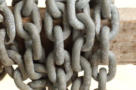chandler: Pattern of thick rusty chain hang on wooden rail. Stock Photo