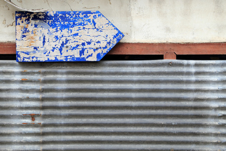 guidepost: Rusty corrugated iron and dirty wall with grungy blue arrow guidepost.