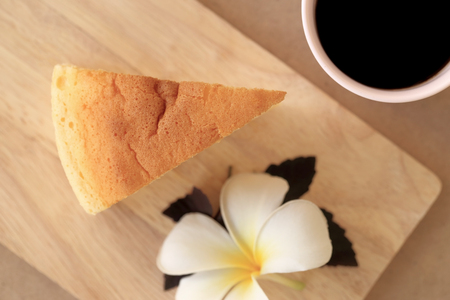 asia style: Pieces of Japanese style Cheesecake and cup of black coffee, top view on wooden plate.
