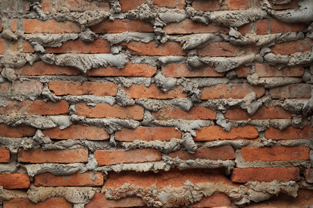 suffusion: The old brick wall with overflow cement at edge joint for background. Stock Photo