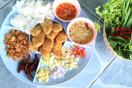Complementing fish recipe - deep fried fish served with spices and herbs side dishes, fresh vegetable and spicy sauce.