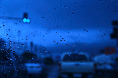 lonelyness: Abstract blurred scene of Road view through car window with rain drops, blue toned color, evening overcast atmosphere.