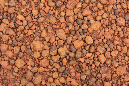 Red laterite gravel texture for background.