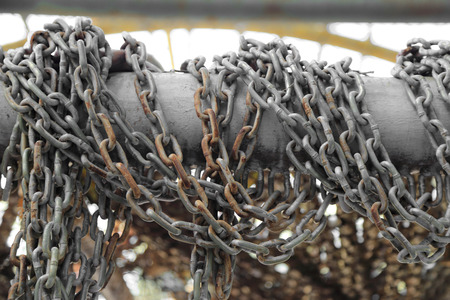 Pattern of thick rusty chain hang on iron rail.