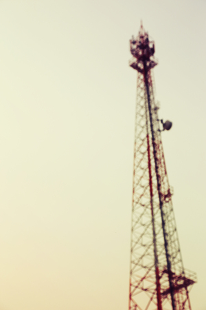 megawatt: Vintage toned and blurred electricity power post tower on pale white sky background.