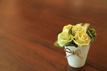 Artificial roses in small pot on wooden table with space for text.