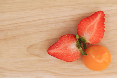 Cape gooseberry and strawberry on wooden background with space for text.