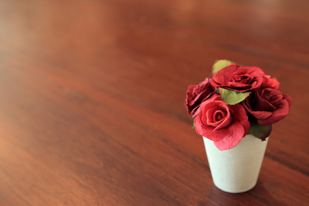 Red artificial roses in small white pot on wooden table with space for text.