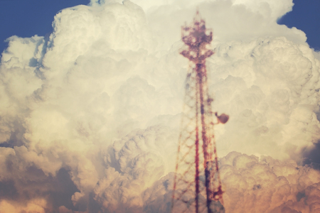 Blurred scene of electricity power post tower overlap on white cloud, concept and vintage toned image. Stock Photo