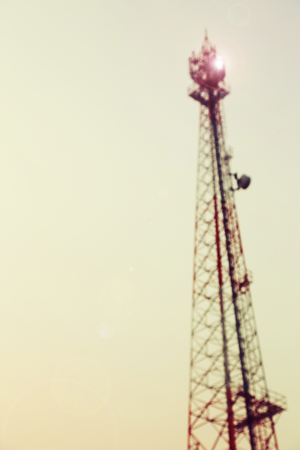 Vintage toned and blurred electricity power post tower on pale white sky background.