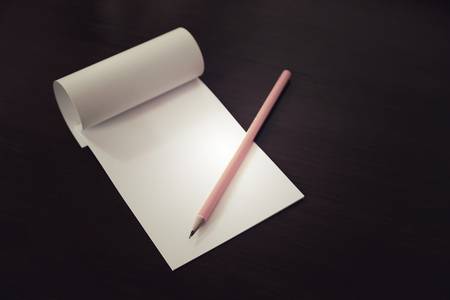 Pencil laying on blank note paper, Creative work, writing, drawing concept. vintage dark toned.