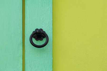 Front view of metal antiques style door handle on wood panel with paint wall, two toned green color. Stock Photo