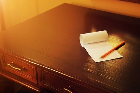 Pencil and blank note paper on old wood table, Creative work, writing, drawing concept. vintage toned with warm light flare image.