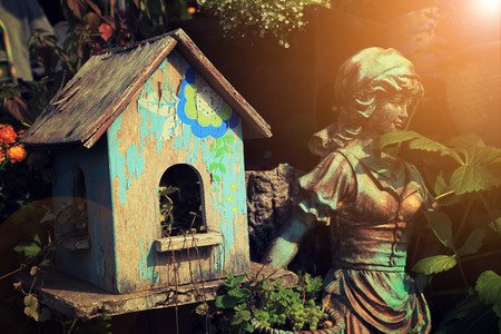 Old blue birdhouse in garden with warm light flare. Stock Photo