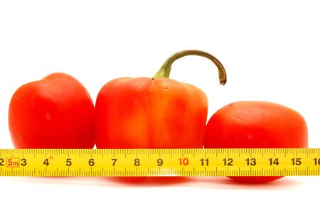 Pepper, tomato and ruler on a white background       photo