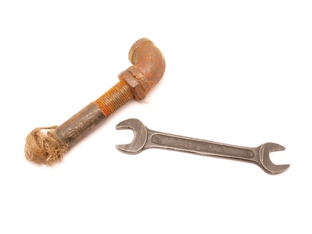 Old a pipe and a wrench on a white background   photo