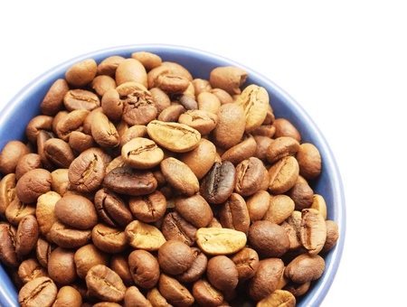 Coffee grains in a blue cup on a white background photo