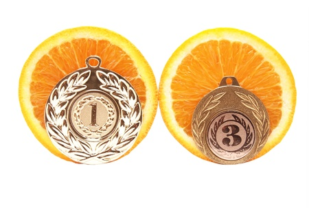 Medal and an orange on a white background photo