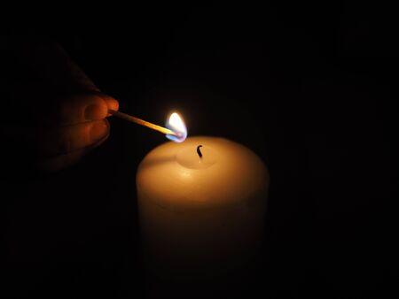 lit: candle lit match on a black background Stock Photo