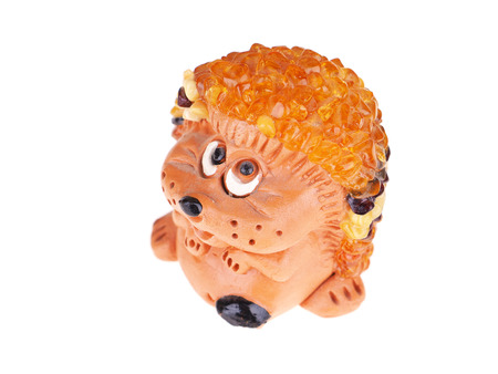 Toy hedgehog made of amber on a white background