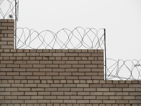 wire fence: brick fence with barbed wire Stock Photo