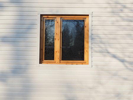 wooden window on white siding background