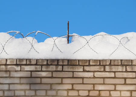 brick wall with barbed wire in the snow Banco de Imagens - 118551112