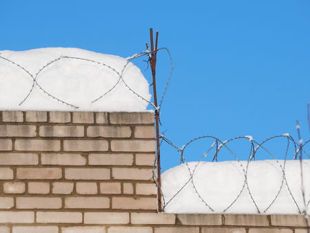 brick wall with barbed wire in the snow