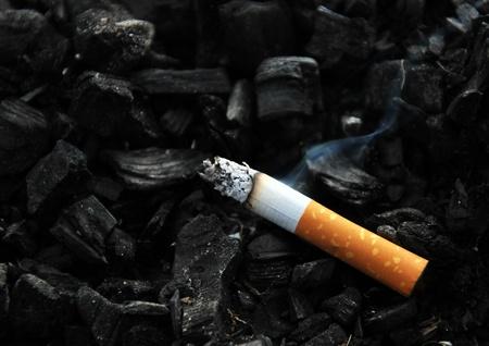 pernicious: Burning cigarette with smoke on black background Stock Photo