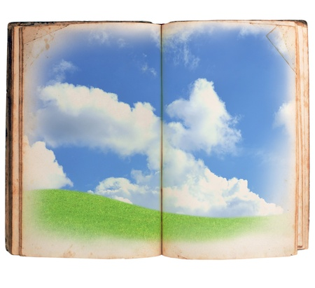 Open book with green meadow and clouds isolated on white background photo